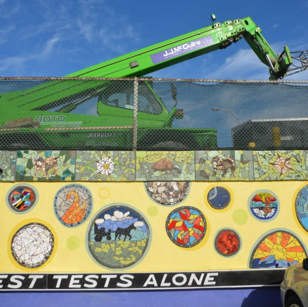 A wall with a chainlink fence above it, a large green construction crane is behind the wire fence. The wall has been covered with a mural, yellow background and mosaic pictures on it. A quote runs along the bottom at ground level, white letters on black background,