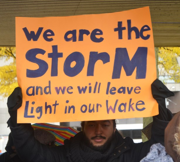 people at a rally protesting against Donald Trump as President of the USA, a man holds up an orange sign with black letters that say We are the storm and we will leave light in our wake
