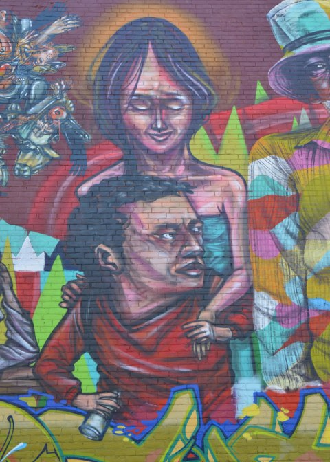 part of a larger mural of elicser and Troy Lovegates, colourful people, A woman stands behind a seated man.