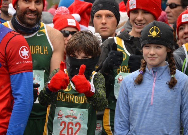 Holly Jolly Fun Run, before the Santa Claus parade, runners getting ready to start the race - a boy with black scarf over most of his face, wearing red gloves, gives a two thumbs up