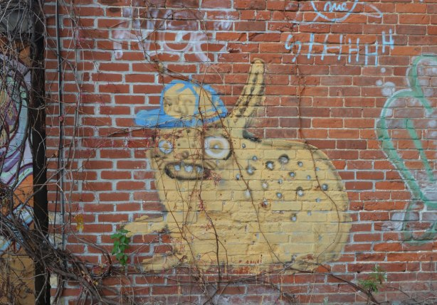graffiti painting of a yellow animal like creature wearing a blue and yellow baseball cap. The creature is yellow. On a red brick wall, with spots on its back
