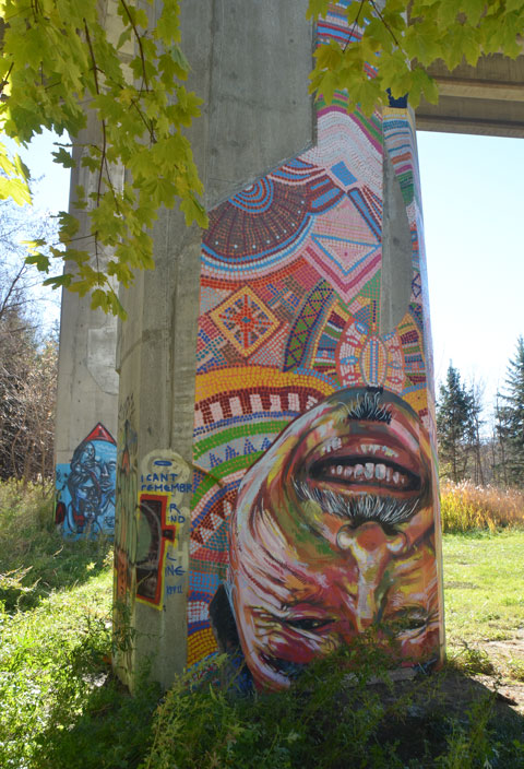 street art on a concrete support pillar of a bridge, a man upside down, large head with top of head on the ground, feet up in the air. moustache, smiling mouth,