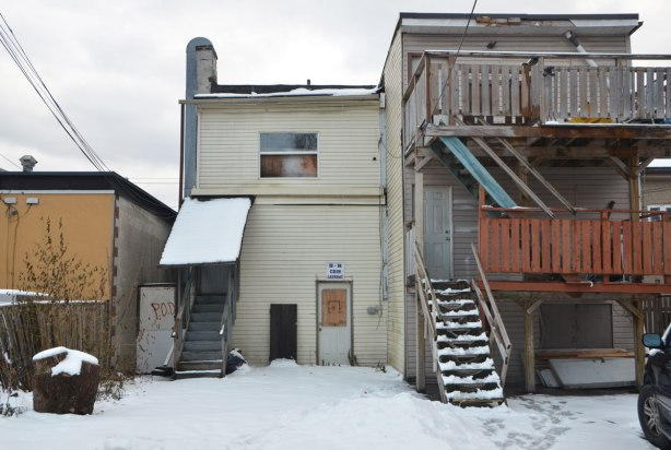 the back of two buildings, one has undeisturbed snow behind it and a sign over the door that says R Coin Laundry. The building beside it (and attached to it) is three storeys high. The upper two levels have a wood railing and balcony out the back. Snow on the ground but lots of foot steps in the snow.