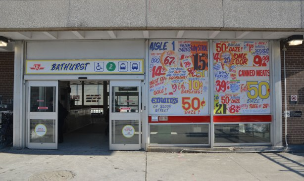 sign maker from Honest Eds store has redone some of the signs in Bathurst subway station plus, he has added some Honest Ed type promo signs around the station - on the window of the station, The window beside the main entrance has been covered with fake ads.