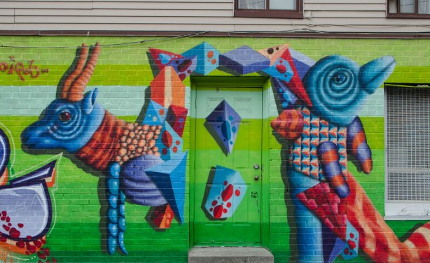 mural by birdo, bright green background with abstract colourful animals painted on it, tall large animals