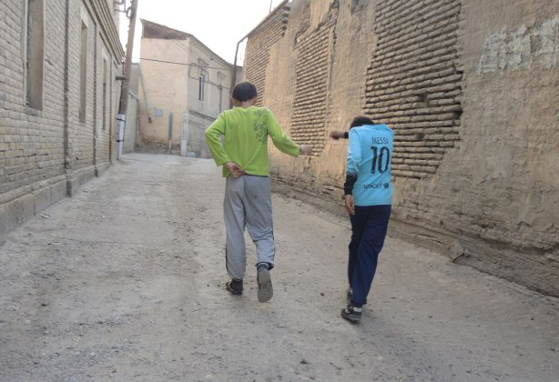 two boys laugh as they walk away, walking down a street with a tall stone wall on one side, and old houses on the other
