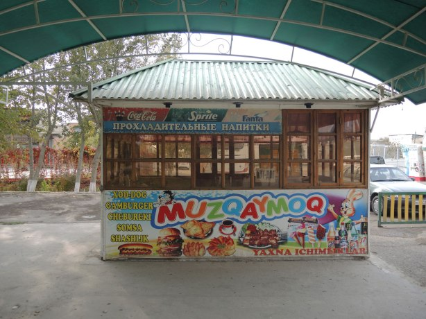 an empty hot dog stand in an amusement park in Bukhara, large pictures advertising what food it sells, hot dogs, hamburgers, fast food