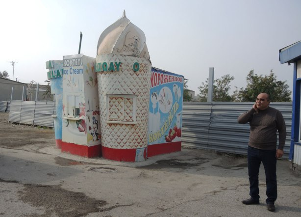 a deserted and boarded up ice cream kiosk at an amusement park in Bukhara, the building is in the shape of a ice cream cone and milkshake.