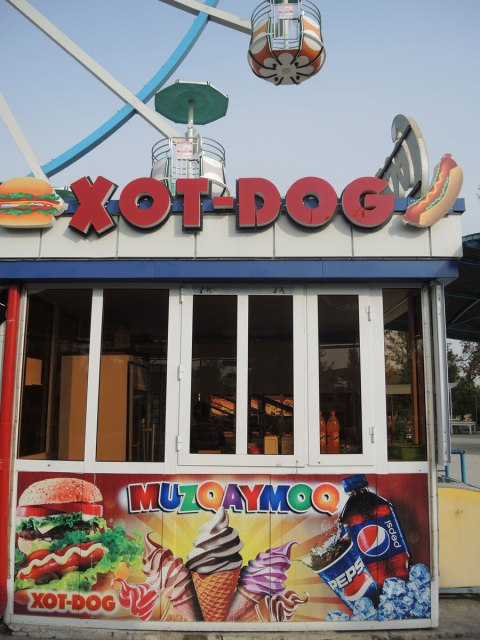 a hot dog stand in an amusement park in Bukhara, where hot is spelled xot as the x in Uzbek language is pronounced close to an H sound.
