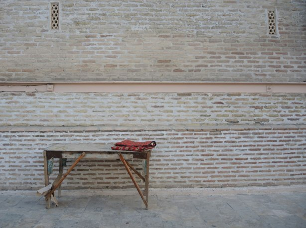 an old brick wall, an old wood bench, and a folded red carpet at one end of the bench.