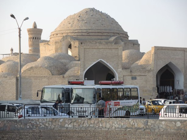 dome shaped building in the historic center of Bukhara with many buses parked in front,