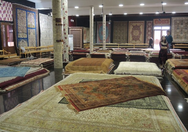 The inside a carpet showroom in Bukhara with many carpets of different sizes stack on the floor and hanging on the walls. Almost all the walls are covered.