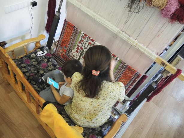 a woman is working on a loom, making a carpet, a young boy sits with her playing games on a smartphone