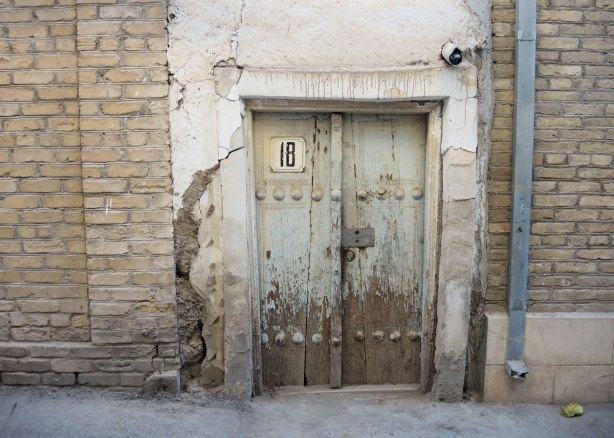 an old wood door with peeling light turquoise paint, on an old stone building, with the number 18 on the door.