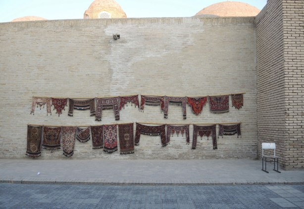 small carpets for sale, strung up against on old brick wall outside, the carpets are designed to fit over the top of a doorway, mostly in dark red and browns,