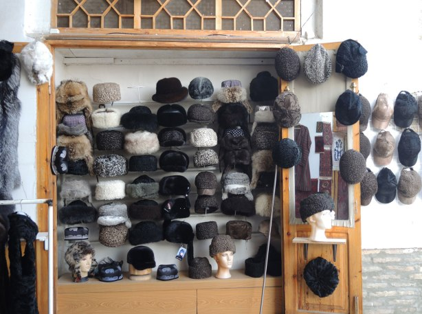 Against an outdoor wall, many fur hats for sale in Bukhara Uzbekistan