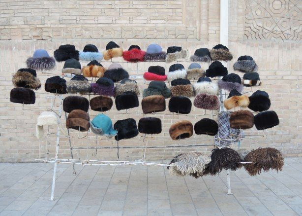 Against an outdoor wall, many fur hats , some are dyed shades of blue or red, for sale in Bukhara Uzbekistan