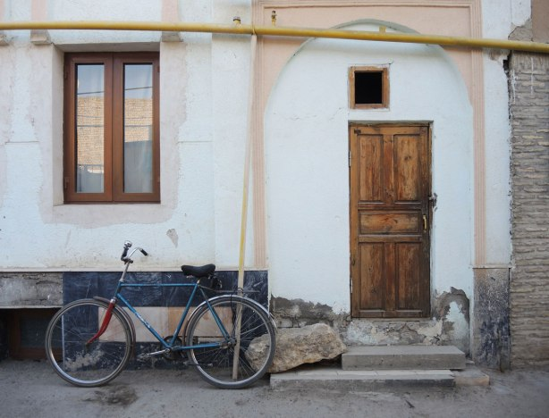 an old house, greyish white, with a wood frame window and old wood door. A bike is parked outside the door. Stone step, yellow pipe for gas runs above the doorway