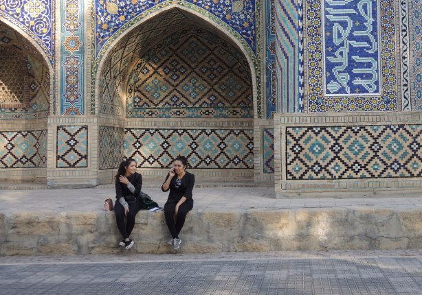 two young woman sitting outside a madrassah. One is sticking her tongue out as she talks on her phone, the other is laughing.
