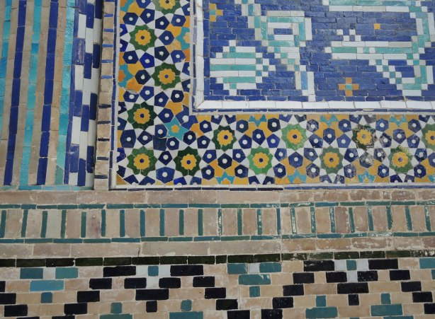 detail of patterns of rectangles and pentagon and hexagon shaped tiles in blue, yellow, black and white, on the front of a madrasah in bukhara