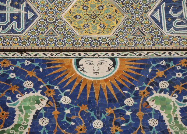 phoenix and sun made of mosaic tiles over the entrance of a madrassah in Bukhara, the Nadir Divan Begi Madrasah - close up picture of the face on the sun