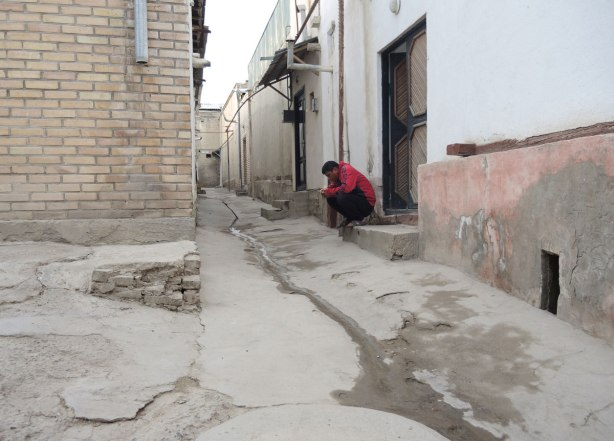 a man in a red sweatshirt sits on a front step, looking at his phone, in an alley with old buildings.