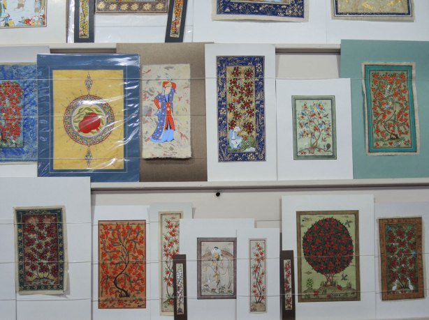 a selection of miniature paintings on the wall of a store. Most are of trees with apples or pomegranates on them.