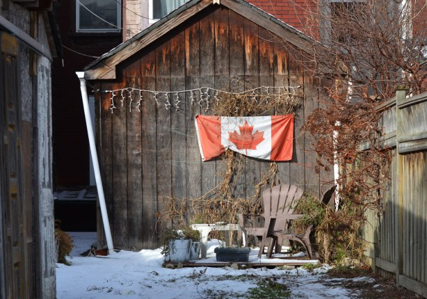 view into a backyard from an alley, some snow on the ground, a Canadian flag is hung on a wall over two brown plastic Muskoka chairs and a small patio table. A string of Christmas lights is above the flag.