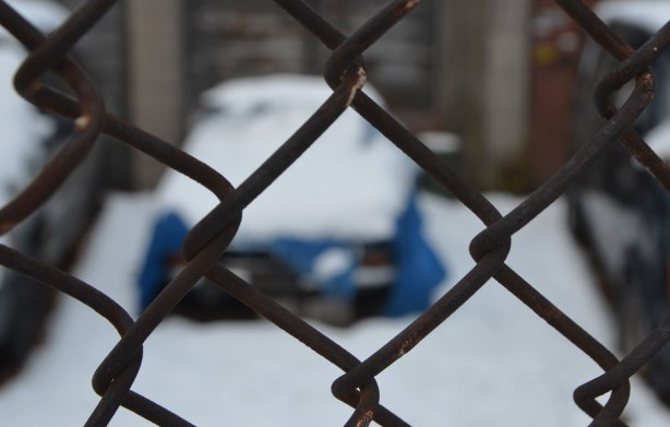Close up of chainlink fence, rusty, but in focus. Out of focus behind it is an old blue car that is covered with snow. It is parked between two black vehicles.