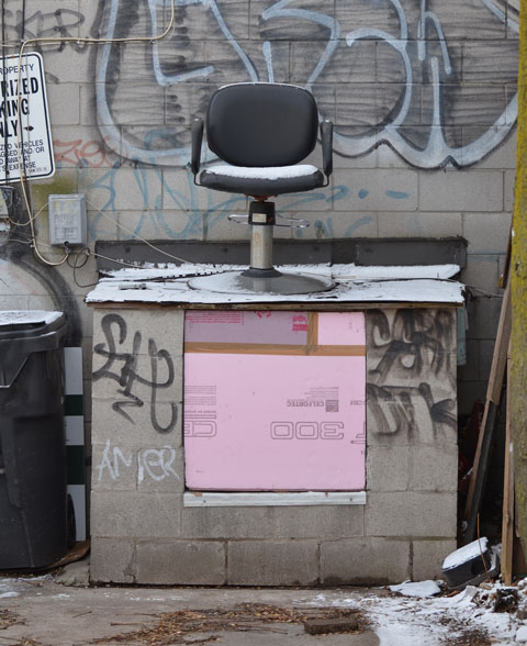 an old office chair with black padded back and seat sits up on a small trash bin made of concrete blocks. A light dusting of snow covers all surfaces