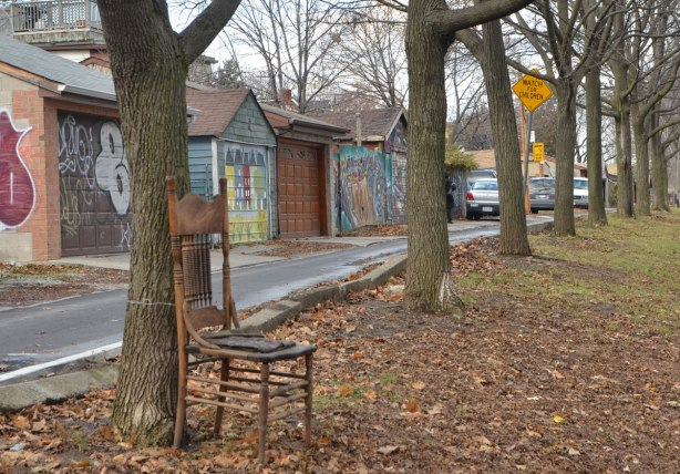 a wooden chair is tied to a tree, autumn leaves on the ground, a row of garages in the background, a number of large trees,