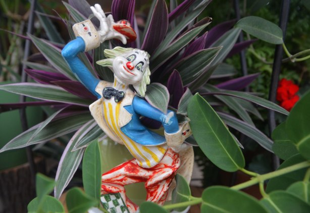 A small figurine of a clown holding his hat above his head, blue jacket, red pants, black bowtie, small figurine in front of a plant with green and purple leaves.