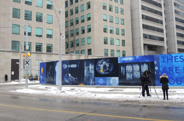 part of mural on a snowy corner, photos in blue tones, a CBC cameraman and reporter are standing on the sidewalk in front of the mural