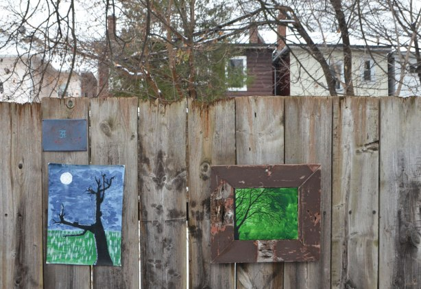 small amateur paintings displayed on a wood fence, with trees and houses in the background, snowy day, Craven Road, trees on blue and green background