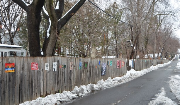 small amateur paintings displayed on a wood fence, with trees and houses in the background, snowy day, looking down the length of most of the gallery, small pile of snow against the fence, painting in the foreground is warm Caribbean sun on beach with palm tree, Craven Road
