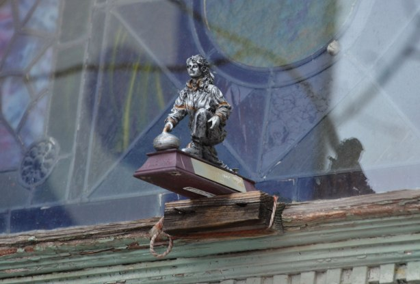 an old weathered curling trophy sits on a window ledge, where it has been tied on. Window behind, reflection of the trophy in the window.