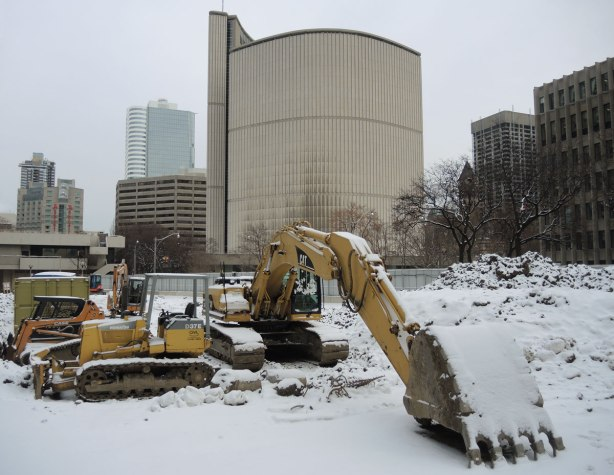 a yellow digger, not working at the moment, sits in a vacant lot, slightly snow covered, the back of Toronto City Hall is in the background.