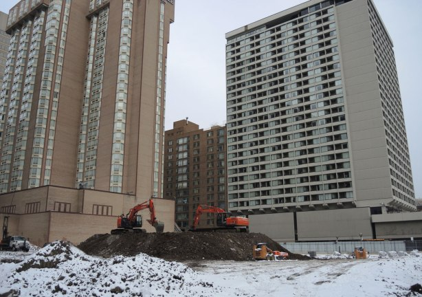 two red diggers on top of a pile of dirt on a snow covered vacant lot, large multirise buildings in the background