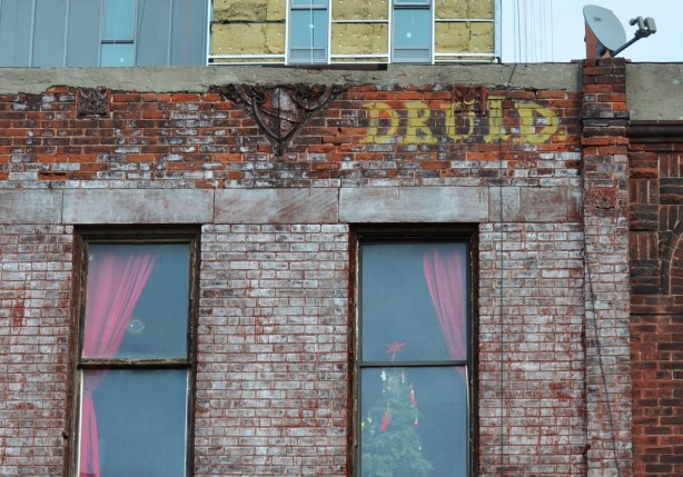 top part of a brick building, two windows, a Christmas tree in one of the windows, the word druid written in yellow spray pain above the windw, a new condo being built in the background