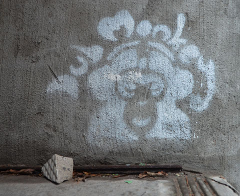 white stencil on a concrete wall that says dub monkey with the face of a monkey