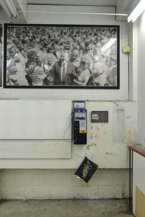 interior of Honest Eds store as it gets ready to close down. An old picture of Ed Mirvish surrounded by a crowd of people hangs on a wall above a Bell payphone.