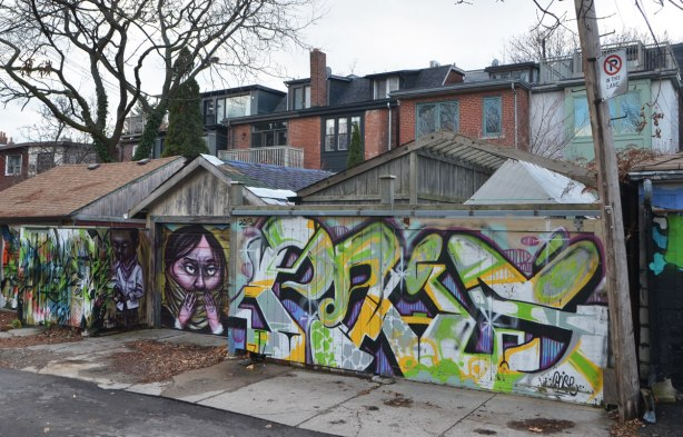 street art on a garage and fence by elicser and poise in a lane,