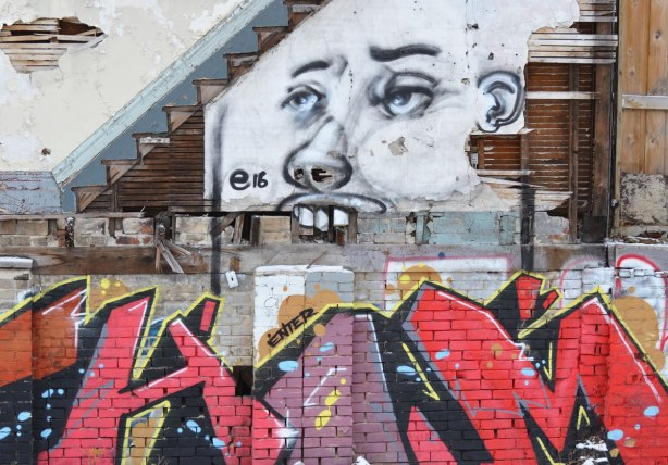 street art painting of a face on the side of a building beside a construction site, building is an old house that is empty. face is painted under the marks on the wall where the stairs were, and teeth are loose bricks hanging vertically. a red and purple throw up text graffiti is in front of the painting.