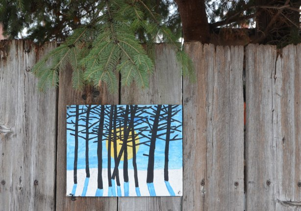 small amateur paintings displayed on a wood fence, with trees and houses in the background, snowy day, an evergreen bough hangs over the top of the fence, above a painting of trees in a forest in winter, low sun, and long blue shadows.