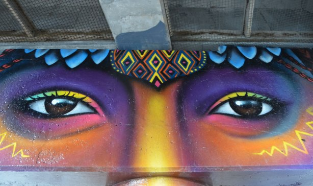 pillars and supports under an overpass that have been painted in bright colours by smoky and shalak - a face showing eyes and top of nose