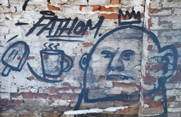 graffiti by Fathom on a brick wall at a construction site, line drawings in black of a man's face, a steaming cup of something hot, and a popsicle. Like hot and cold.