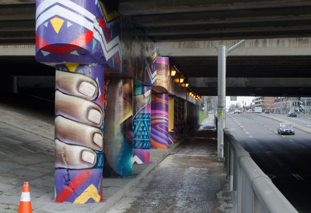 pillars and supports under an overpass that have been painted in bright colours by smoky and shalak - a large face in the center pillar, with hands gripping the outer pillars on each side of the face