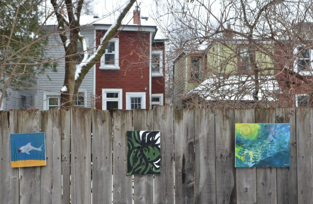 small amateur paintings displayed on a wood fence, with trees and houses in the background, snowy day, three paintings, one is a fish