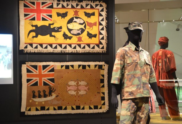 two flags displayed on a black background, with two male mannequins dressed in military Ghanese costume.
