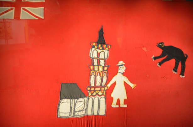 close up of a flag, hand made, British Jack in the top left corner, a man walks in front of a church in the center, a black bear in the top right.